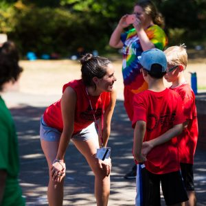 Staff smiling and talking to two campers in the red group.