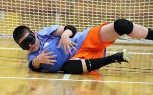 Blind Athlete Stopping Ball in Goalball