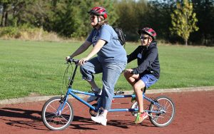 Blind Child Riding Two Seat Bicycle with Female Guide