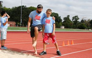 Camp Counselor Instructing Visually Impaired Athlete in Long Jump Techniques