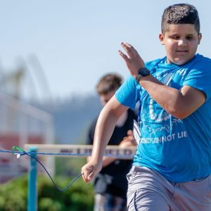 youth running using tether attached to string to guide him in a straight line; blue skies in background