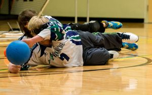 Two Blind Athletes Blocking a Shot in a Competitive Game of Goalball
