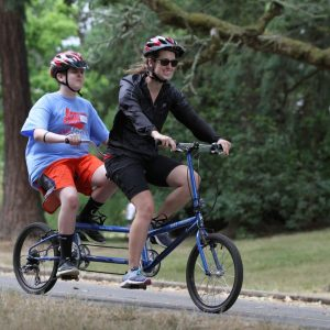 Coach and camper tandem biking with smiles on their face.