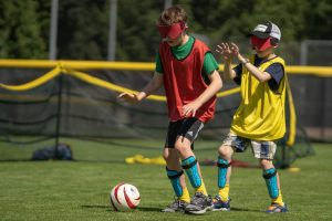 two youth playing soccer with eye covers on a field with trees in background