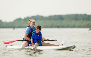 Small Child Sitting on Stand-up Paddle Board with Adult Guide