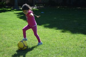 Young Girl Playing with Yellow Soccer Ball