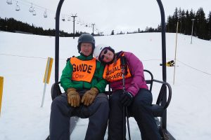Visually Impaired Skier Ridding Lift with Guide