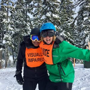 Prateek and volunteer, Kathy, smiling in front of snow-covered trees on ski day