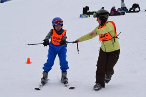 Athlete holding ski pole while volunteer guide directs