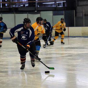 Hockey player passing puck across ice