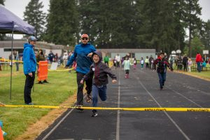 Boy running in front of volunteer guide approaching finish line