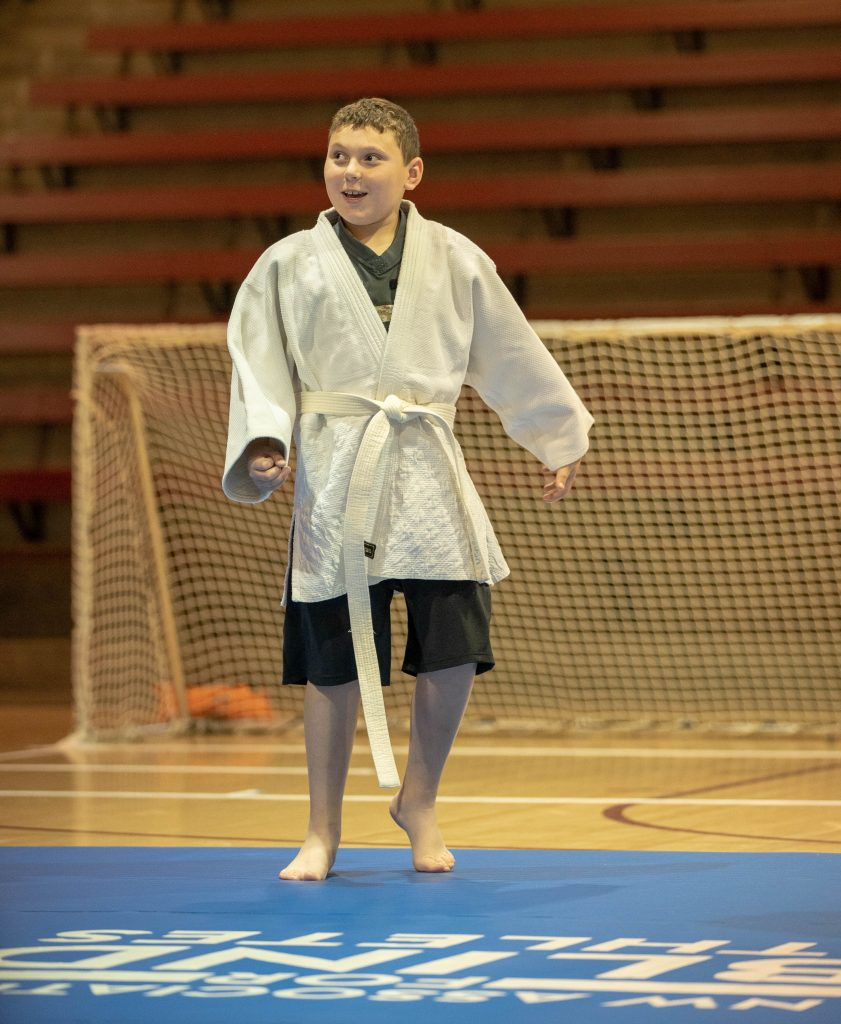 Judah smiling and walking across judo mat in a gym