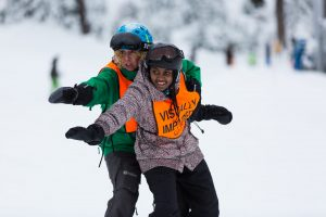 Ski guide and NWABA youth athlete leaning together with right arms out on a snowy mountain, trees in the background