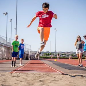 youth athlete jumping high into sandpit while other camp counselors watch; red track and blue skies in background