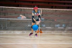 youth playing goalball throwing the ball in front of her goal in an indoor gym